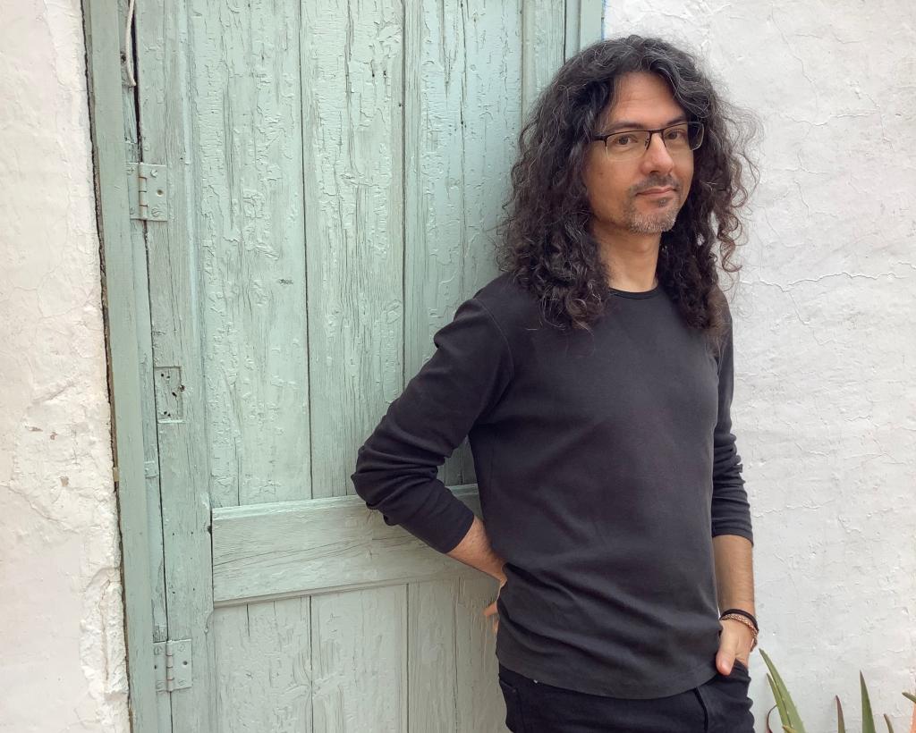 Jaime Martín posando frente a una puerta azul con una camiseta negra.